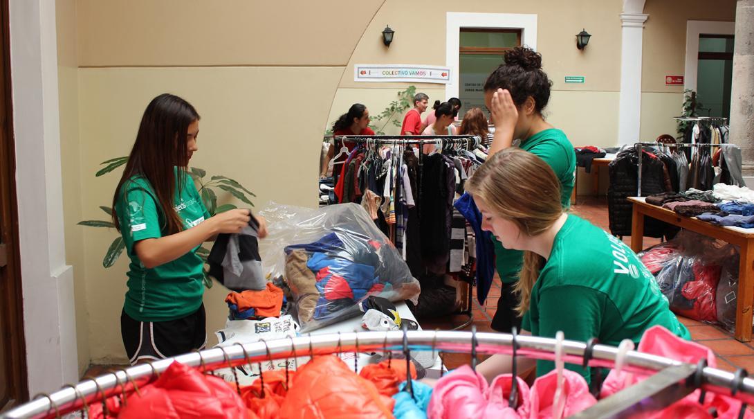 Voluntarios ayudando a distribuir ropa a migrantes